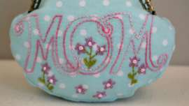 The word Mom embroidered on a small blue polka dot coin purse