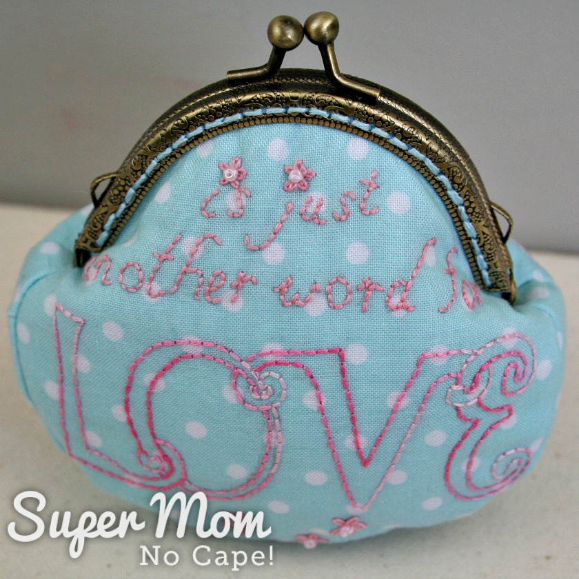 Small blue with white polka dot coin purse with the word is just another word for Love stitched on it