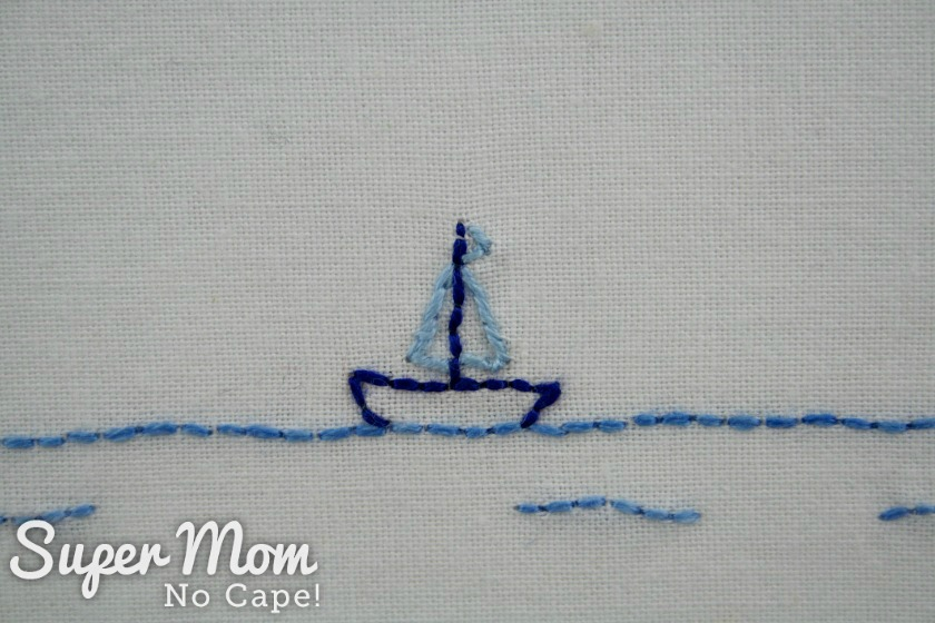 Embroidered dark blue sailboat with light blue sails