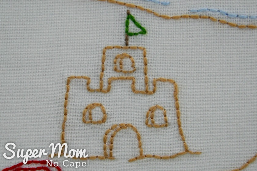Embroidered sand castle with green triangular shaped flag