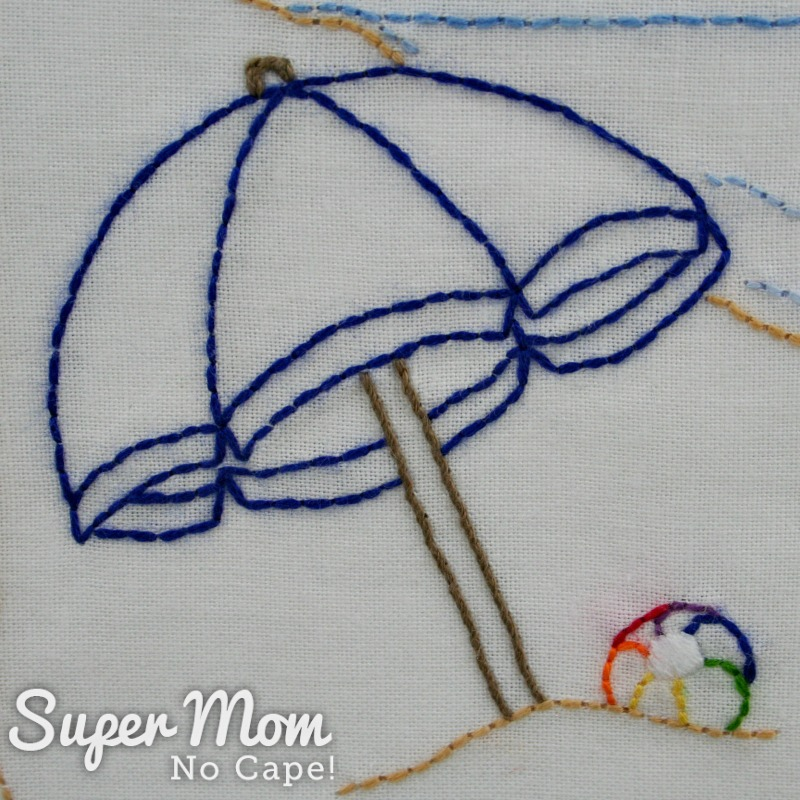 Blue embroidered beach umbrella in sand with beach ball beside it