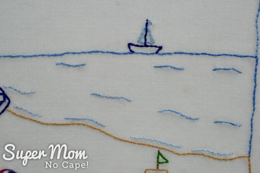 Small embroidered sailboat on gently waving water