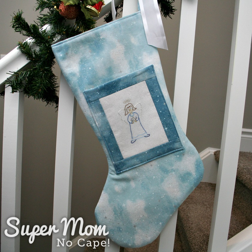 Prudence Angel stocking hung up on a bannister decorated with pine garland