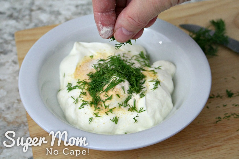 Freshly chopped dill weed being sprinkled on top of Greek yogurt and spices
