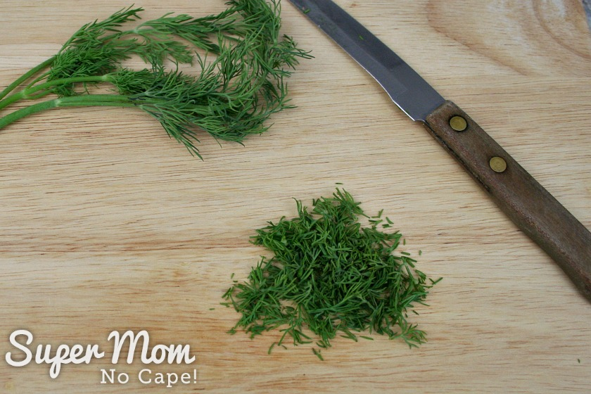 Pile of finely chopped dill weed on cutting board beside a paring knife