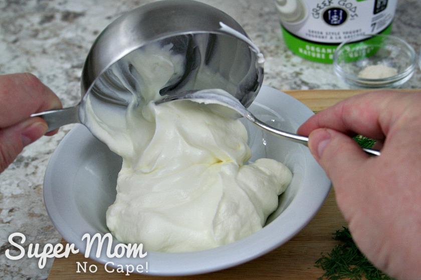Cup of greek yogurt begin spooned into a white bowl