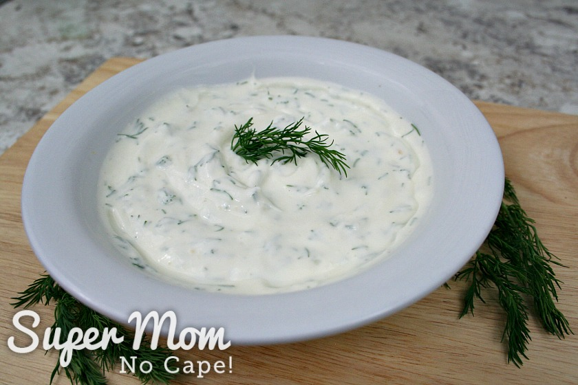 White bowl filled with Dilly Greek Yogurt Dip on a cutting board with dill sprigs