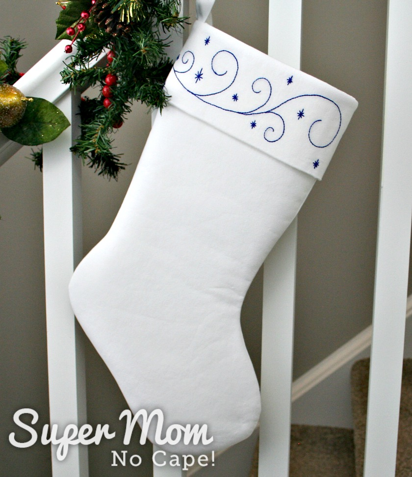 Back of white stocking with Blue Embroidery hanging from a banister.