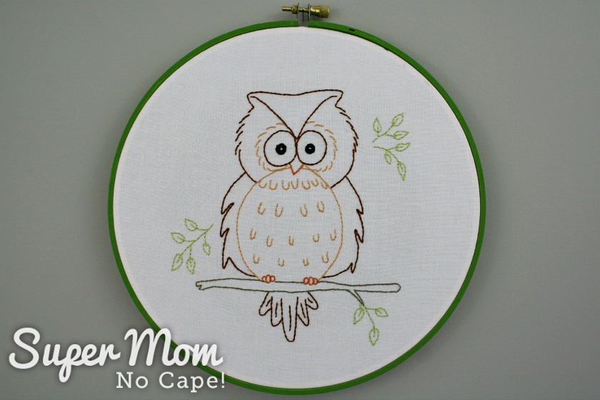 Completed Owain Owl embroidery in an embroidery hoop painted green