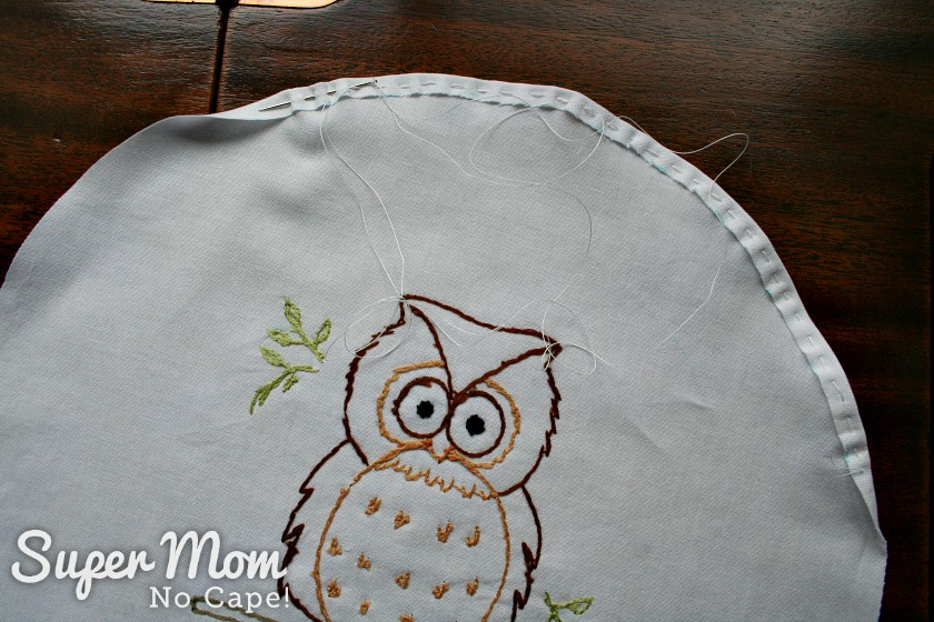 Gathering stitches being worked around the edge of the fabric circle with Owain Owl Embroidery Pattern stitched on it