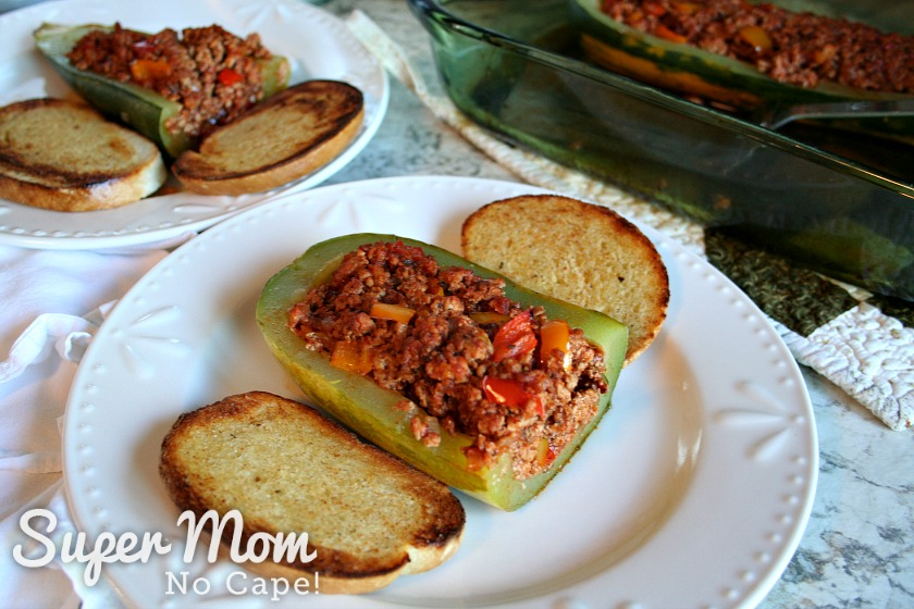 Half of Sausage stuffed zucchini with toasted bread on white plates
