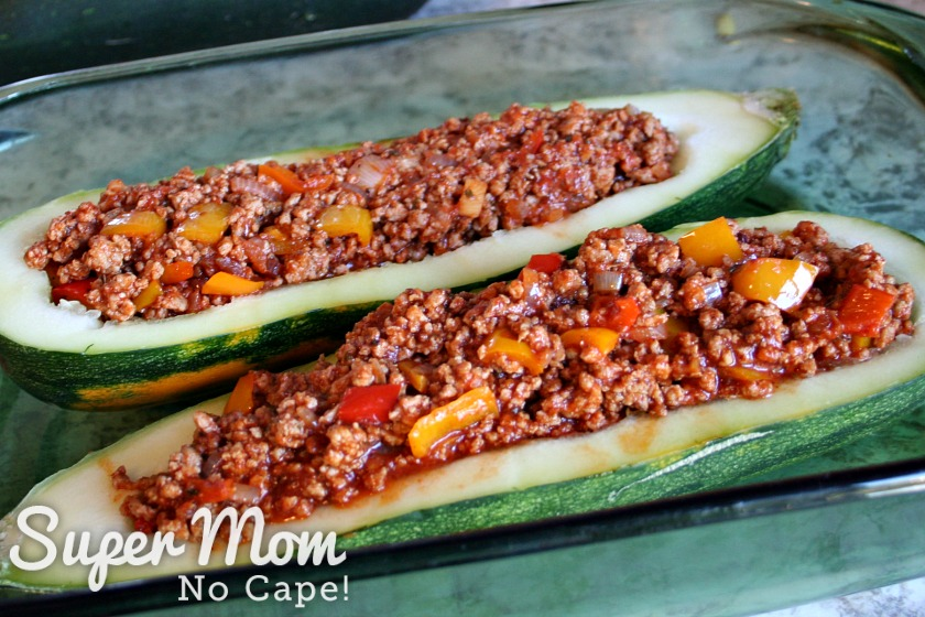 Two halves of a hollowed out zucchini with meat filling in a baking dish