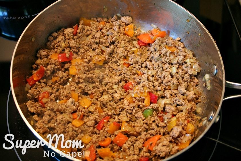 Sausage meat mixture for stuffed zucchini pizze boats cooking in a frying pan