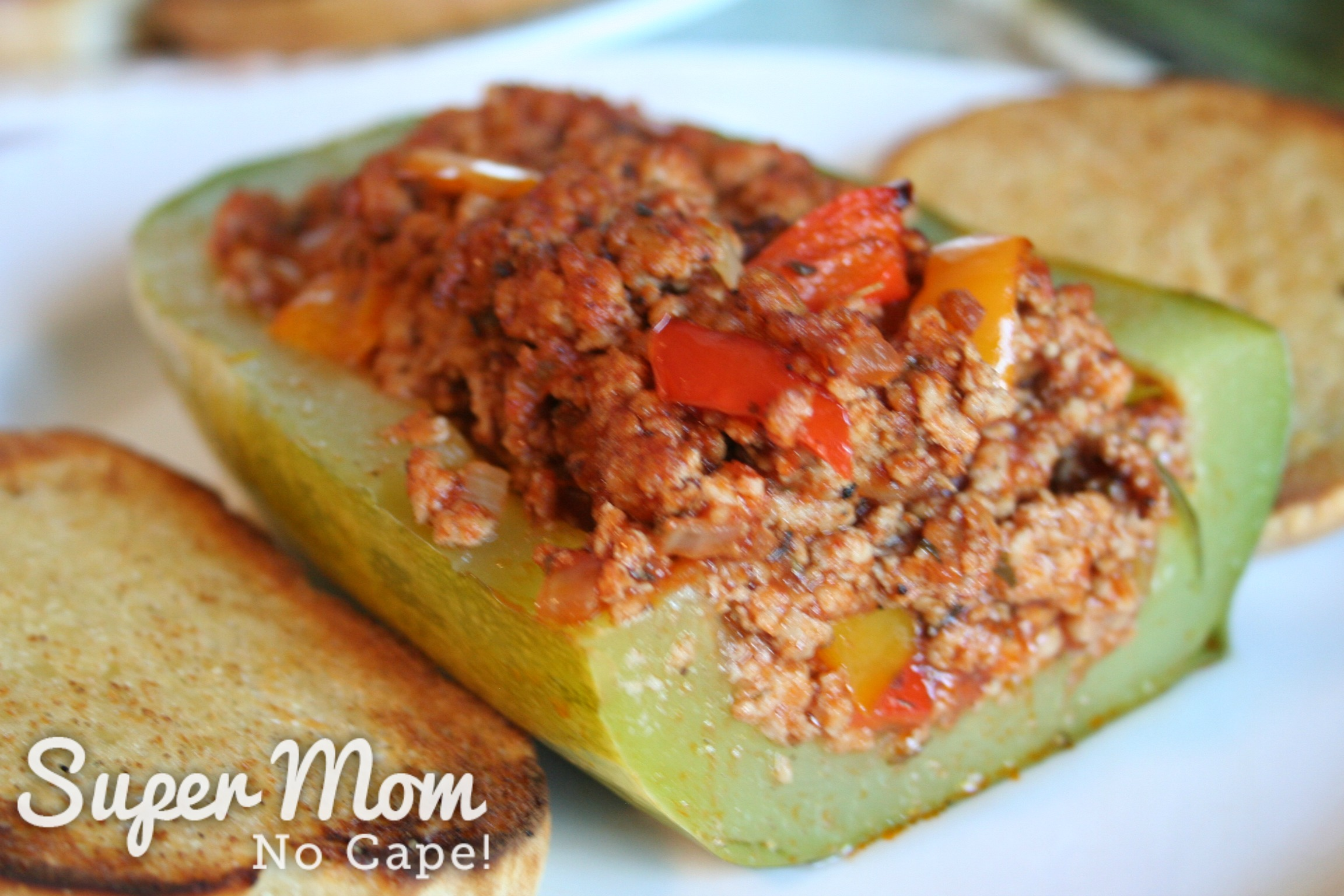 Half of a Sausage Stuffed Zucchini Pizza Boat with toasted bread on a white plate