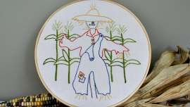 Hoop Art Strawbyn Scarecrow Embroidery Pattern with dried corn cobs in the background