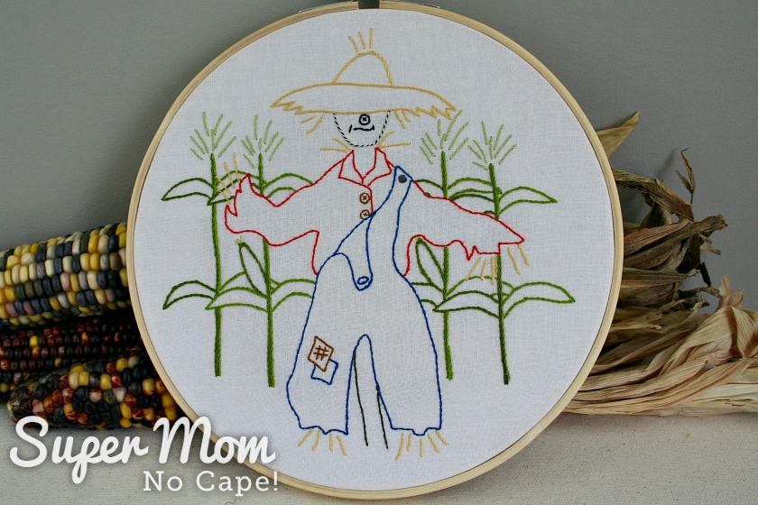 Scarecrow embroidery leaned against dried corn cobs