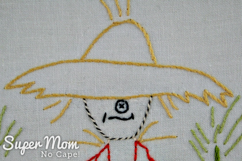 Embroidered straw hat and face of Strawbyn Scarecrow