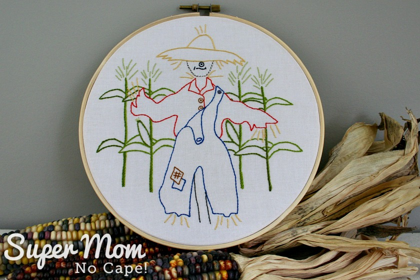 Strawbyn Scarecrow hoop art placed on top of 3 dried corn cobs