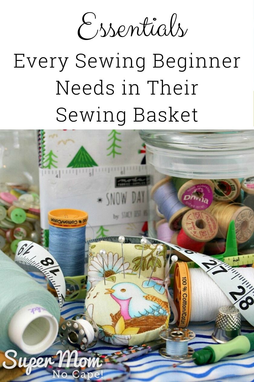Various sewing notions arranged on a stack of blue fabric with text at the top Essentials Every Sewing Beginner Needs in Their Sewing Basket