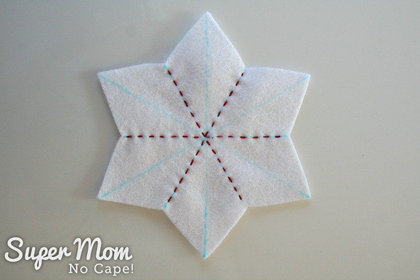 White felt star with three lines of red running stitch.