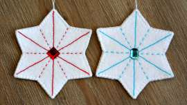 Two white felt stars, one with red embroidery the other with blue embroidery with matching gems in the center of each.