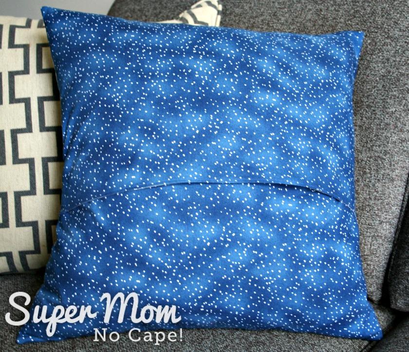 Back of the envelope style pillow cover made with blue fabric with silver dots.