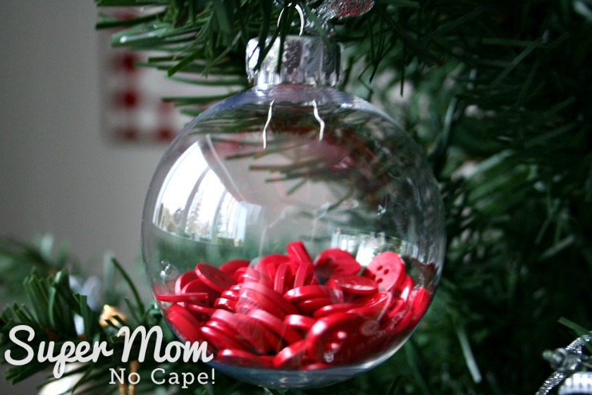Clear plastic bauble with red buttons inside hanging on a tree.