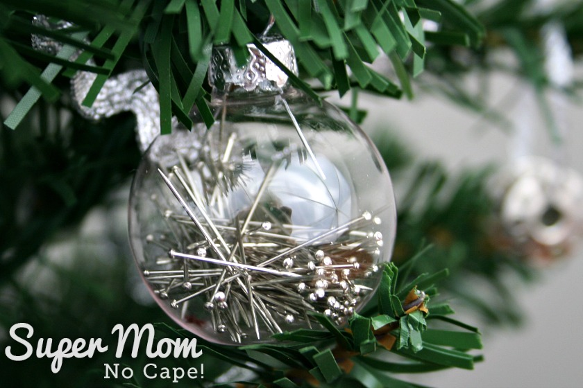 Clear glass bauble with silver straight pins inside.