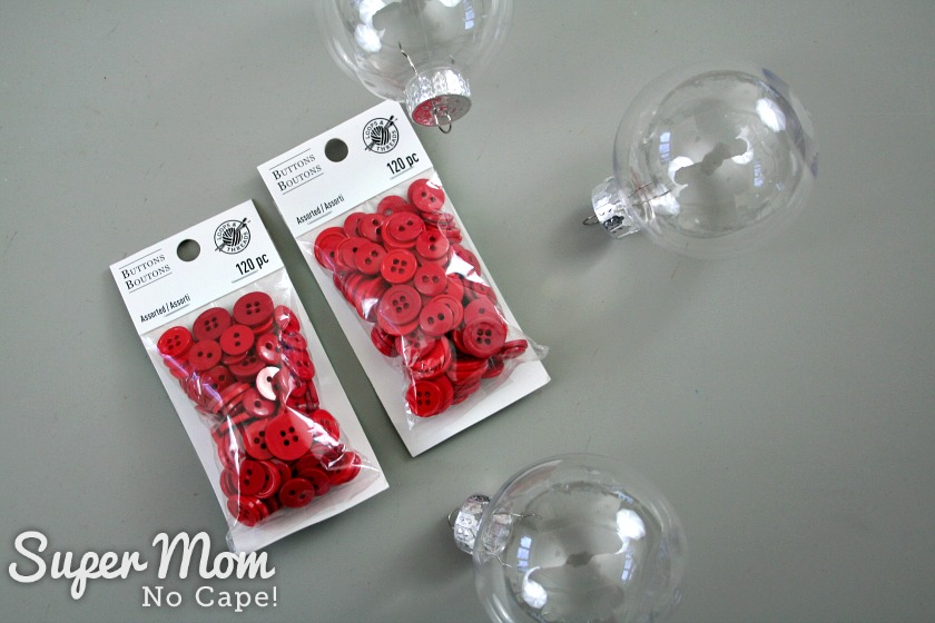 Two packages of red buttons and three clear plastic Christmas baubles