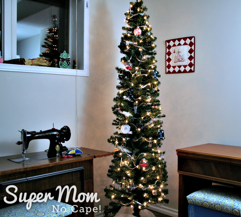 Lighted Sewing themed Christmas tree standing between two sewing machine cabinets.