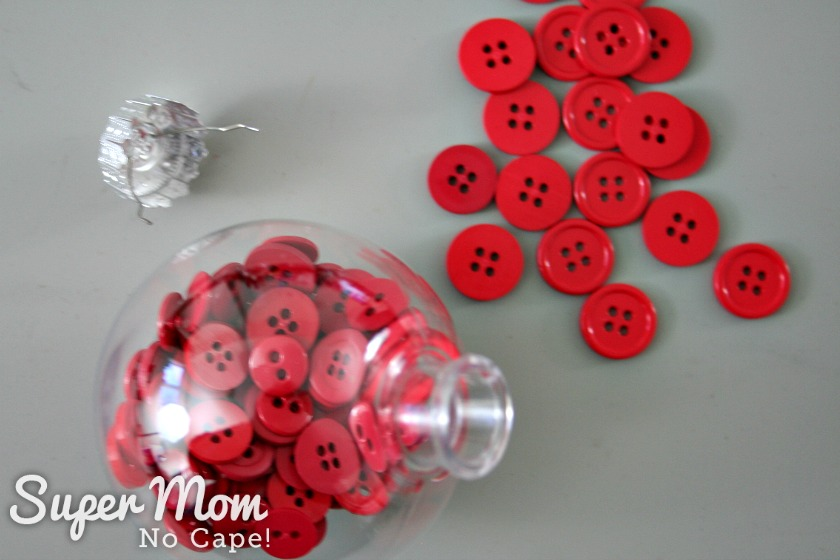 Red button inside a clear plastic bauble, bauble top and more red buttons.