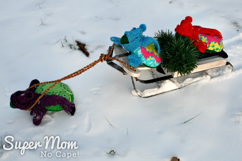 Rexie Hexie Turtle pulling a sled with Lexie and Lanie and their Christmas tree