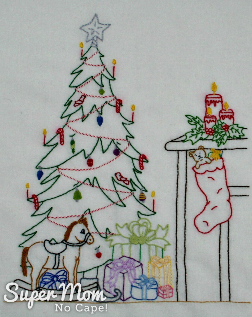 Embroidery of a beautifully decorated tree with gifts underneath beside a fireplace with candles on the mantel and a stocking hung filled with toys.