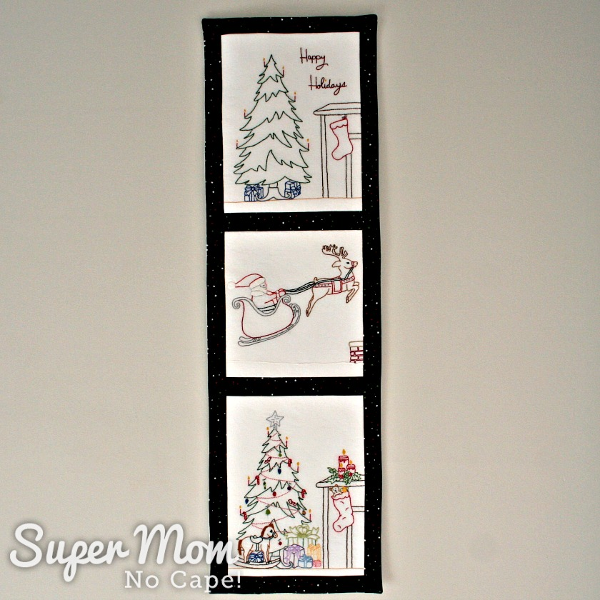 Tall, narrow wall hanging featuring three Christmas embroideries.