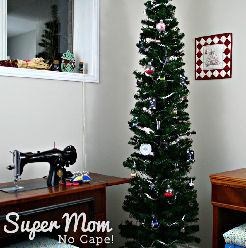 Sewing themed Christmas tree standing between 2 sewing cabinets.