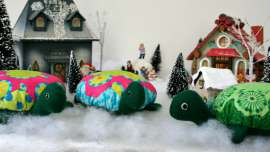 The three Hexie Turtles sitting in front of a Christmas village.