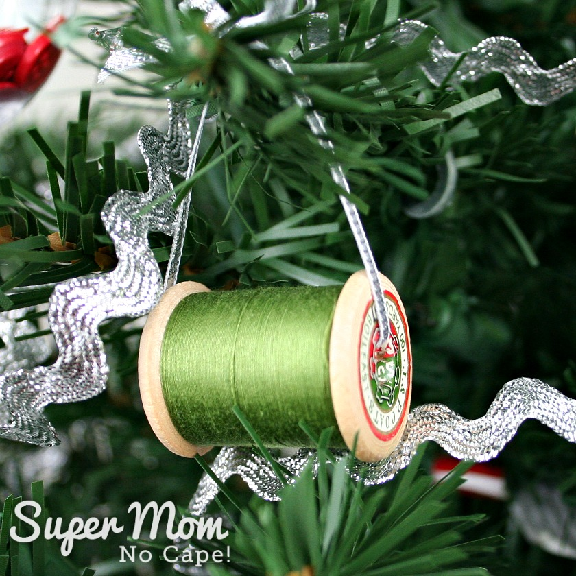 Vintage spool of green thread hung on the sewing themed Christmas tree