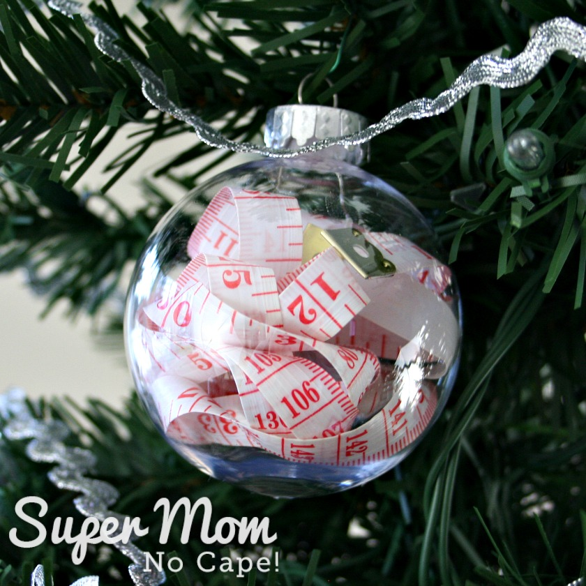 White measuring tape with red lines and numbers inside clear plastic Christmas bauble