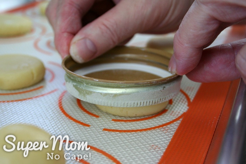 Flattening the almond cookie ball using a jar lid