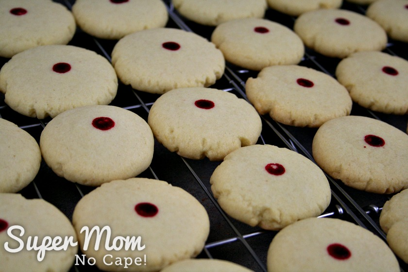 Red dot almond cookies cooling on racks