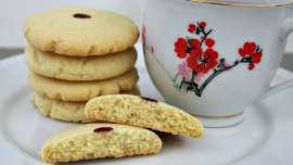 A stack of red dot almond cookies on a white plate with a cup of tea