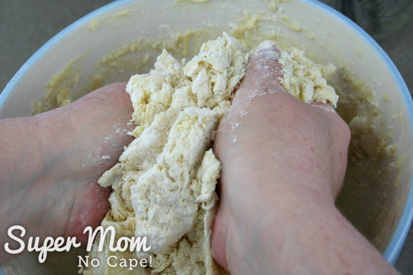 Using two hands to finish incorporating the flour into the butter mixture