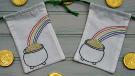 Two drawstring bags with a pot of gold at the end of the rainbow embroidered on them with coins scattered around.