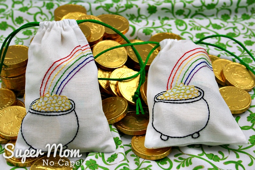 Two full drawstring bags filled with gold wrapped chocolate coins laying on a pile of gold chocolate coins.