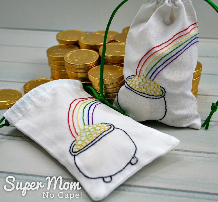 One embroidered bag filled with chocolate coins and a second bag half filled with coins behind both.
