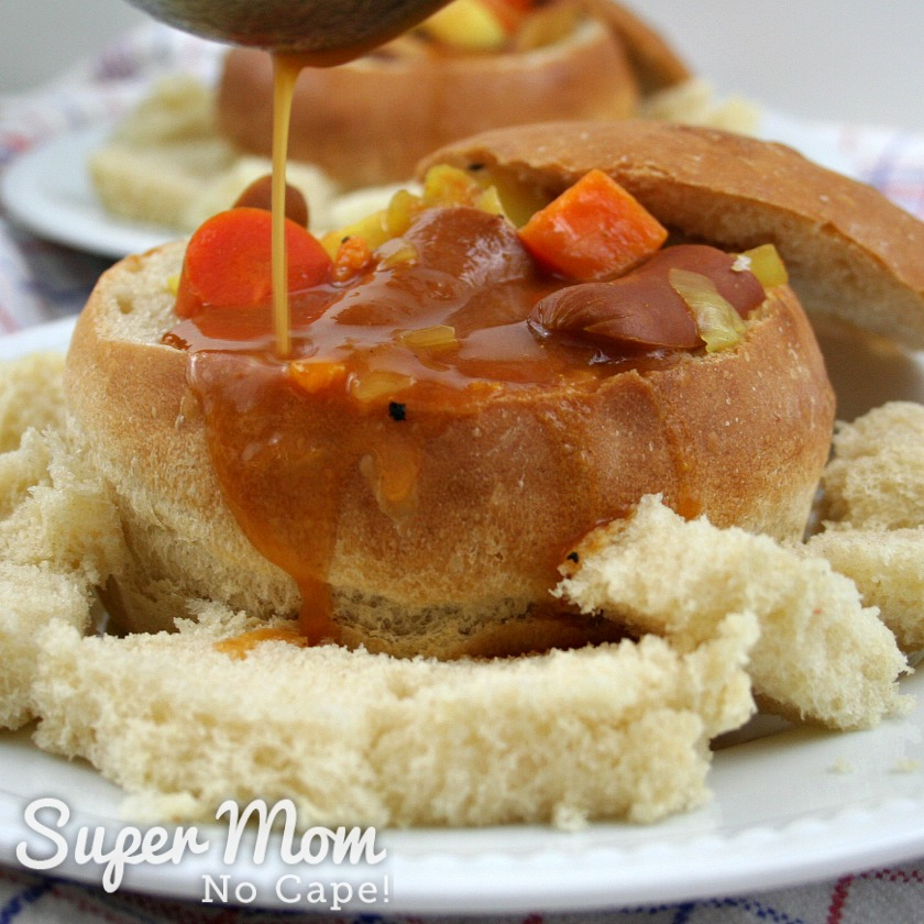 Stream of the wiener stew gravy being poured into stew filled bread bowl