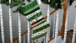 QAYG Stocking hanging on a banister with pine boughs