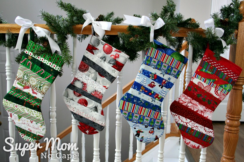 Four quilt as you go stockings in various colored fabrics with toes facing right tied with white ribbon to a stair railing wrapped with a pine garland.