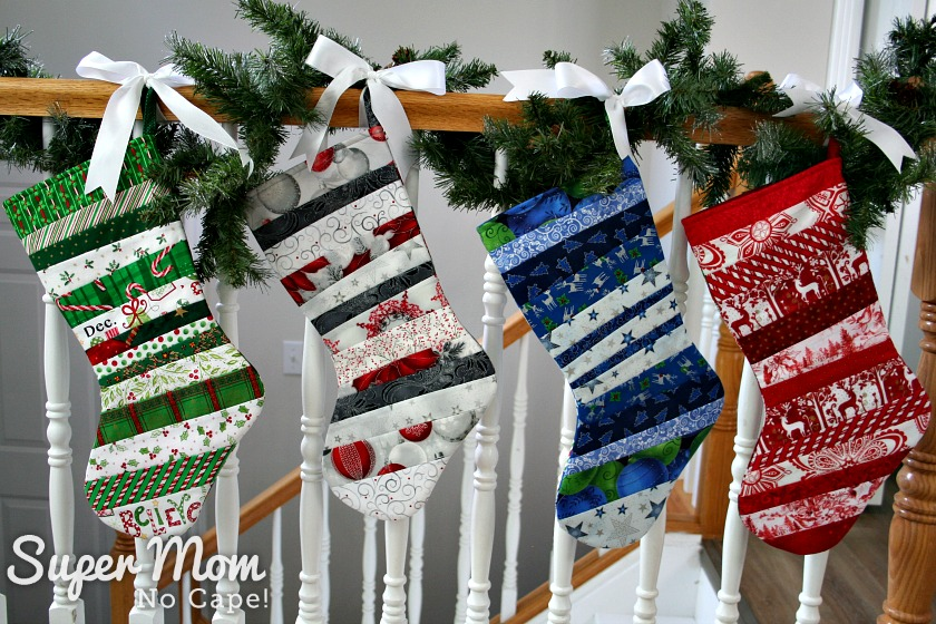 Four quilt as you go stockings in various colored fabrics with toes facing left tied with white ribbon to a stair railing wrapped with a pine garland.