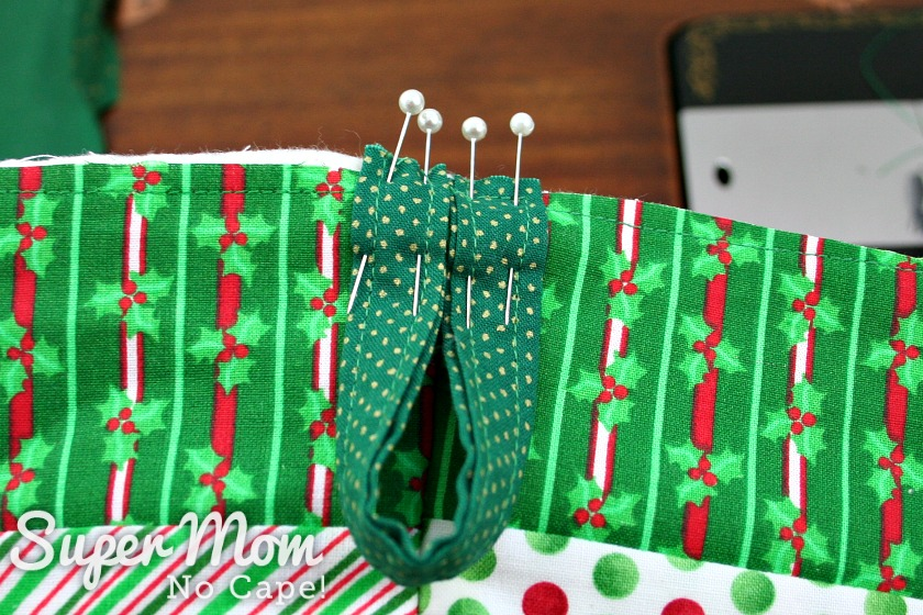 The green hanging loop pinned to the back of the right side of the quilted stocking.